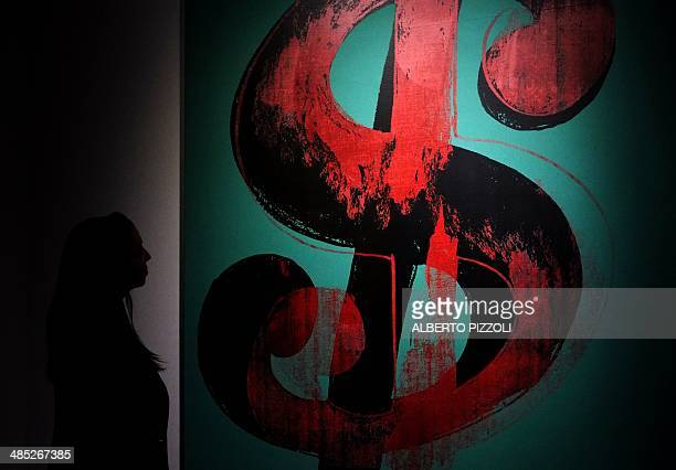 A woman looks at 'Dollar Sign' by US artist Andy Warhol as part of the exhibition 'Warhol' on April 17 2014 in Rome The works of the artist father of...