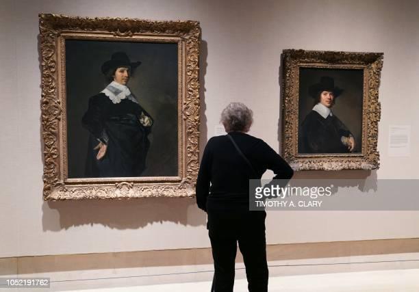 A woman looks at Dutch artist Frans Hals's 'Paulus Verschuur ' and Johannes Verspronck 'Portrait of a Man' during a press previews at The...