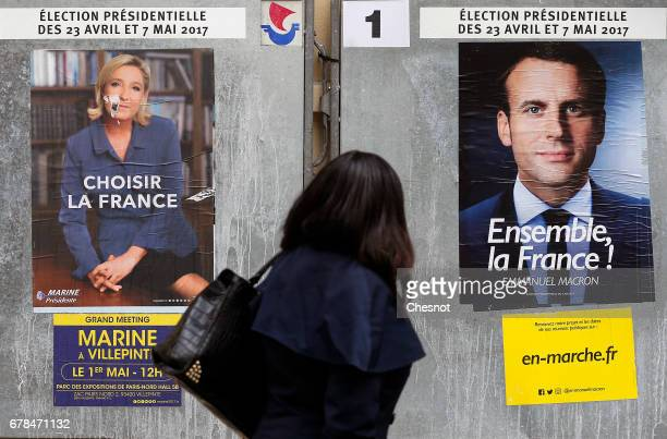 A woman looks at electoral posters of French presidential election for the En Marche movement Emmanuel Macron and President of the National National...