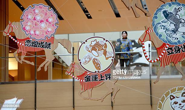 A woman looks at 'ema' showing tablets with horses to mark the zodiac 'Year of the Horse' ahead of the calendar New Year on January 1 decorating a...