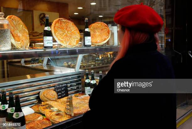 A woman looks at Epiphany cakes or Twelfth Night cake displayed in the window of a pastry shop on January 06 2017 in Paris France The 'galette des...