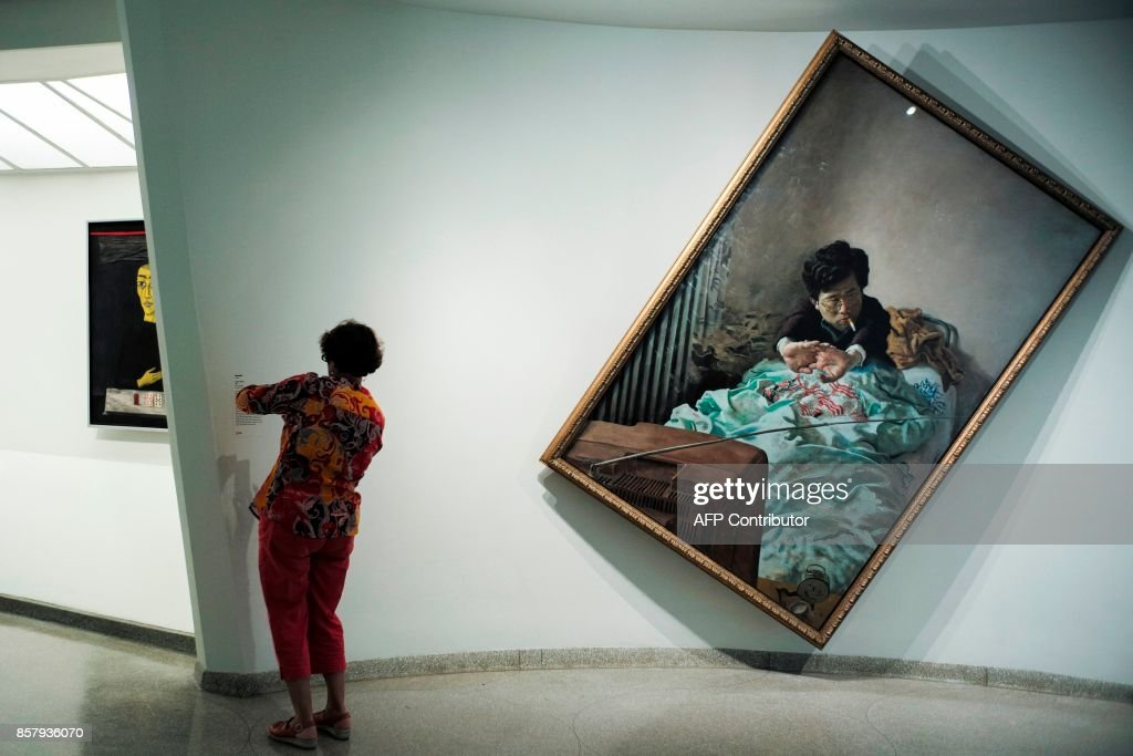 A woman looks at exhibits during the 'Art and China after 1989: Theater of the World' media preview at the Solomon R. Guggenheim Museum in New York on October 5, 2017. / AFP PHOTO / Jewel SAMAD / RESTRICTED