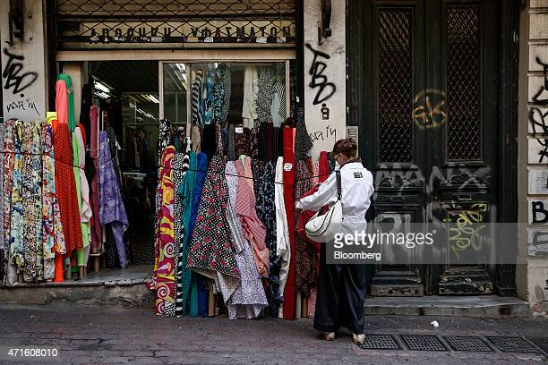 A woman looks at fabrics outside a fabric store in the Agia Irini district of Athens Greece on Saturday April 25 2015 The downturn that decimated the...