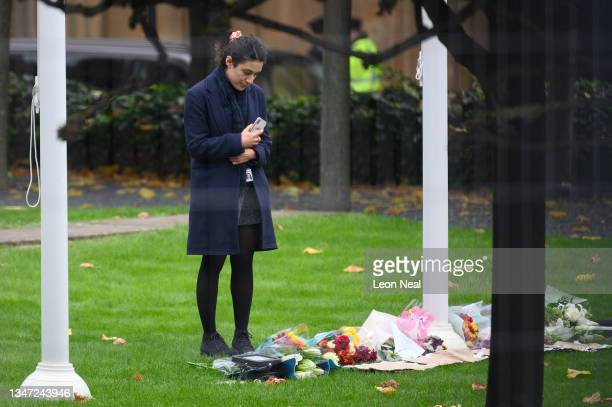 Woman looks at floral tributes laid within the grounds of the Houses of Parliament on October 18, 2021 in London, England. Sir David Amess, MP for...