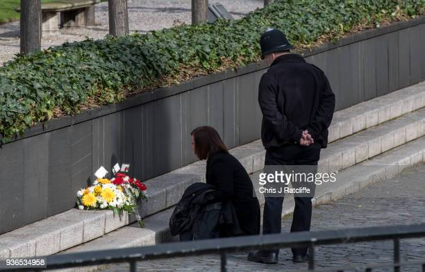 A woman looks at floral tributes left by police officers during a brief ceremony in New Palace Yard inside the gates of the Houses of Parliament...
