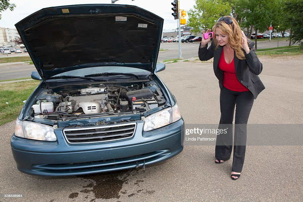 A Woman Looks At Fluid Leaking From Her Car Edmonton Alberta