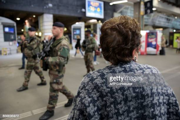 A woman looks at French soldiers as they patrol in the train station Gare Montparnasse in Paris on October 2 2017 as part of the Sentinelle military...