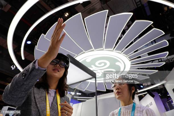 Woman looks at General Electric GE90 high-bypass turbofan aircraft engine with AR glasses during the 2nd China International Import Expo at the...