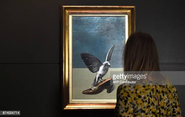 A woman looks at 'God is not a Saint' by Belgium artist Rene Magritte which hides under its layers the missing and final piece of another Magritte's...