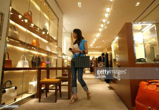 A woman looks at goods at an outlet of the French fashion brand Hermes in Shanghai 19 June 2007 The luxury icon opened a new store to mark its 10th...