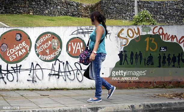 A woman looks at graffitis at the 13 Commune shantytown in Medellin Antioquia department Colombia on July 15 2015 In 2002 Medellin was rocked by...