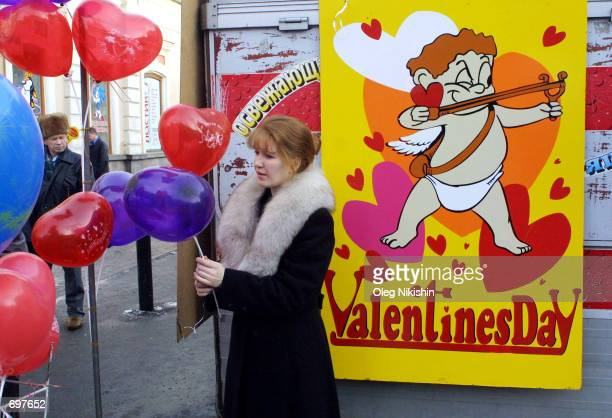 A woman looks at heartshaped balloons for Valentines Day February 14 2002 in Irkutsk Eastern Siberia Russia