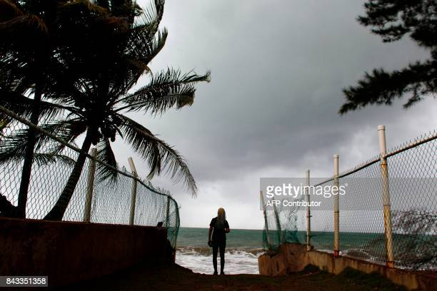 TOPSHOT A woman looks at heavy surf as Hurricane Irma approaches Puerto Rico in Luquillo on September 6 2017 Irma is expected to reach the Virgin...