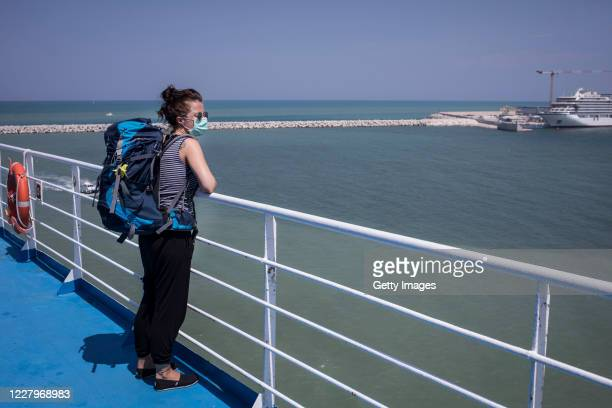 Woman looks at her arrival from the deck of a passenger ship arriving from Greece to port on August 7, 2020 in Ancona, Italy. Passenger ships resume...