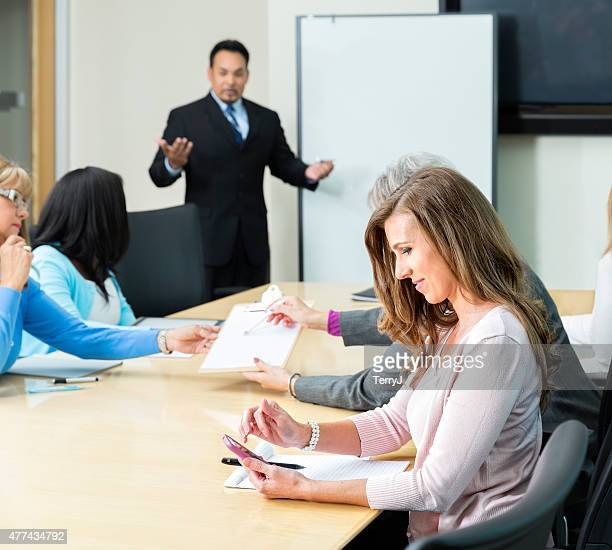 Woman Looks at Her Cell Phone During Business Meeting