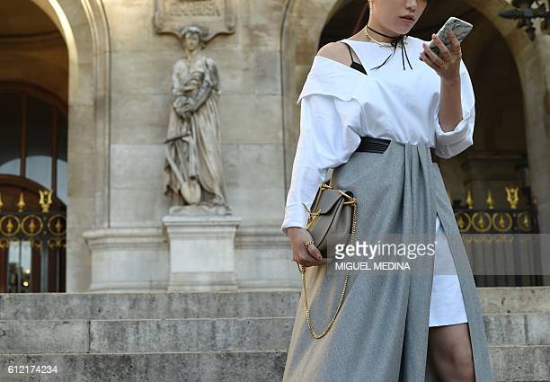A woman looks at her cellphone as she stands on the stairs of the Opera Garnier during the fashion week in Paris on October 3 2016 / AFP / MIGUEL...