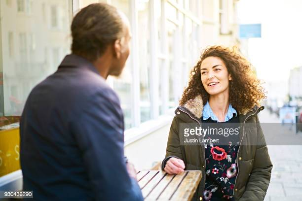 Woman looks at her friend or family member in mid conversation, sitting outside a cafe in the sunshine