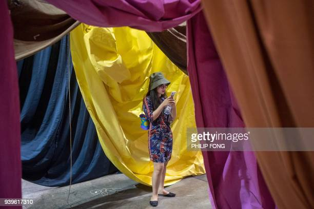 A woman looks at her mobile phone at the exhibit of German artist Ulla von Brandenburg's 7 Curtains at Art Basel in Hong Kong on March 29 2018 / AFP...