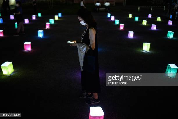 A woman looks at her mobile phone while standing among paper lanterns placed to mark the 75th anniversary of the atomic bombing at a park in in...