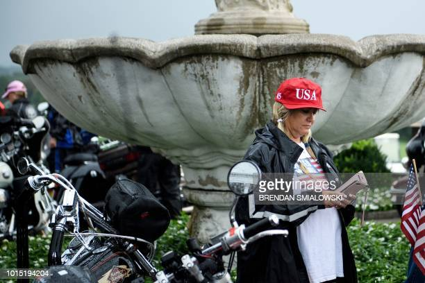 A woman looks at her phone after US President Donald Trump met with supporters during a Bikers for Trump event at the Trump National Golf Club August...