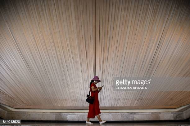 TOPSHOT A woman looks at her phone as she walks inside an exhibition centre in Shanghai on September 8 2017 / AFP PHOTO / CHANDAN KHANNA