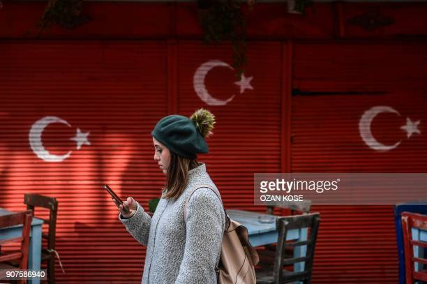 A woman looks at her phone as she walks past a wall with Turkish national flags drawed on January 20 2018 on a sunny day in the Balat district of...