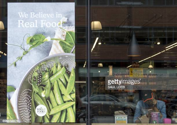 A woman looks at her phone at a Whole Foods Market in Washington DC June 16 following the announcement that Amazon would purchase the supermarket...