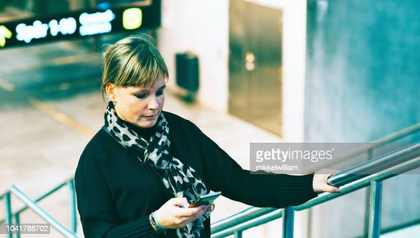 Woman looks at her phone while walking on stairs near public transportation