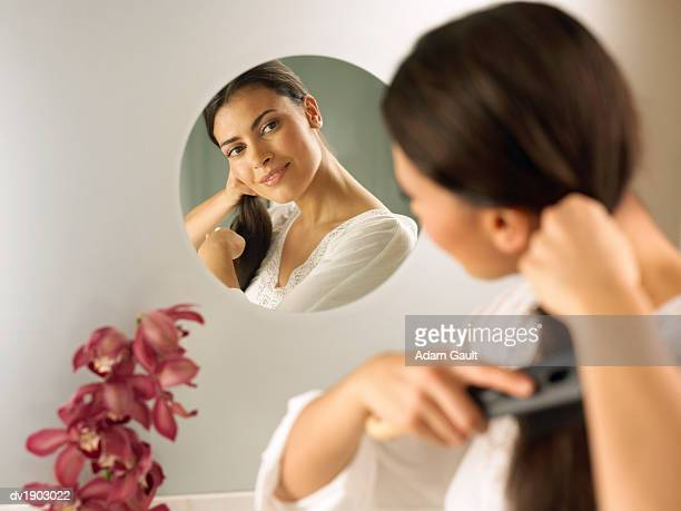 Woman Looks at Her Reflection in Mirror Brushing Her Hair