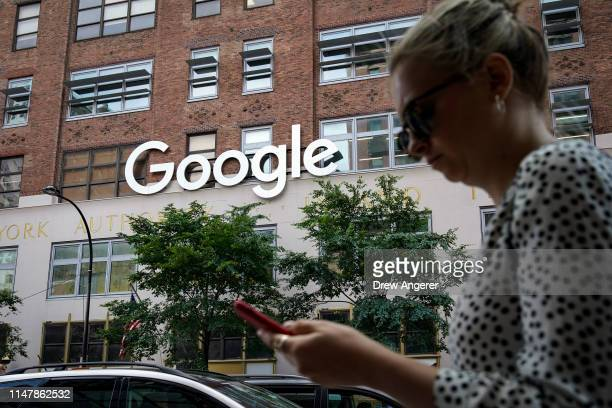 A woman looks at her smartphone as she walks past Google Building 8510 at 85 10th Ave on June 3 2019 in New York City Shares of Google parent company...