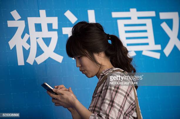 A woman looks at her smartphone during the Global Mobile Internet Conference at the National Convention Centre in Beijing on April 28 2016 GMIC hosts...