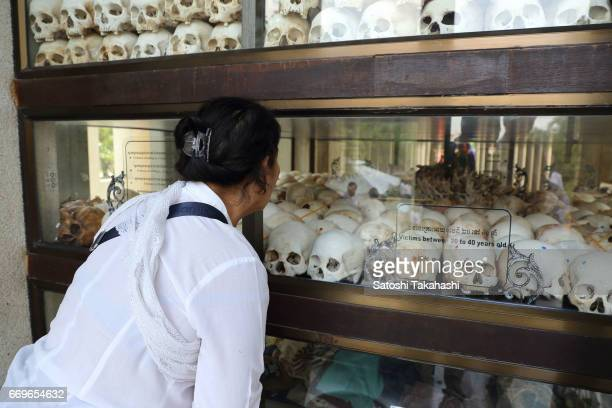 A woman looks at human skulls displayed in a memorial tower at the Choeung Ek killing fields during a memorial service to mark the 42nd anniversary...