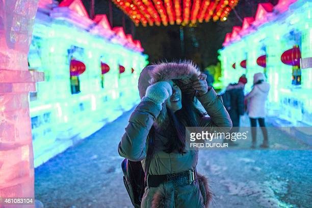 A woman looks at ice sculptures while visiting the Zhaolin Park on January 6 2015 during the 16th Harbin International Ice and Snow Festival in...