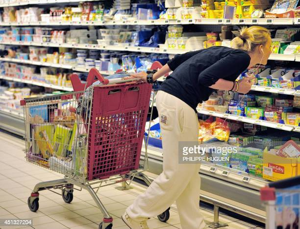 A woman looks at information on products as she buys groceries in an Auchan supermarket a branch of the French international retail group Auchan on...