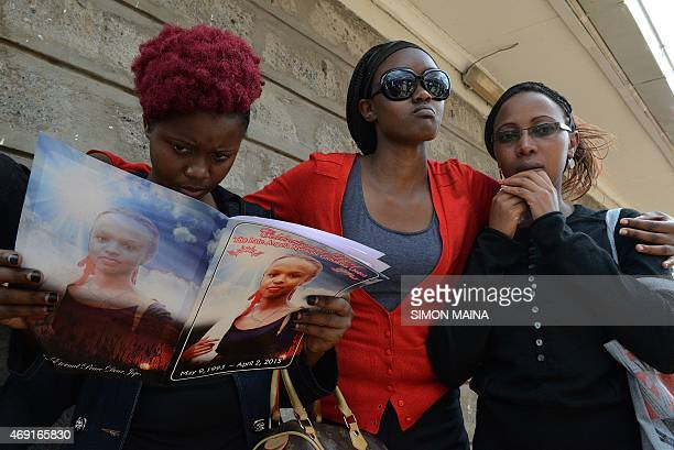 A woman looks at memorial booklet at the funeral of Angela Nyokabi who was killed during the attack on Garissa University at Mutunguru Catholic...