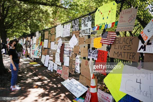 Woman looks at messages attached to the security fence on the north side of Lafayette Square, near the White House, in Washington, DC on June 8,...