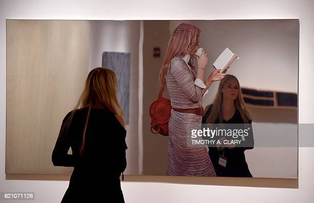 A woman looks at Michelangelo Pistoletto Turista Che Mangia Un Panino on display during the media preview on November 4 2016 for Sothebys New York...