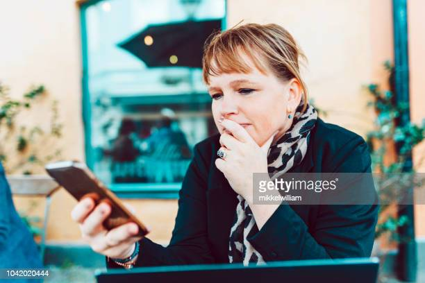 Woman looks at mobile phone while sitting at outdoor cafe