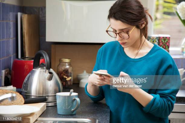 Woman looks at mobile phone while waiting for kettle to boil in kitchen.