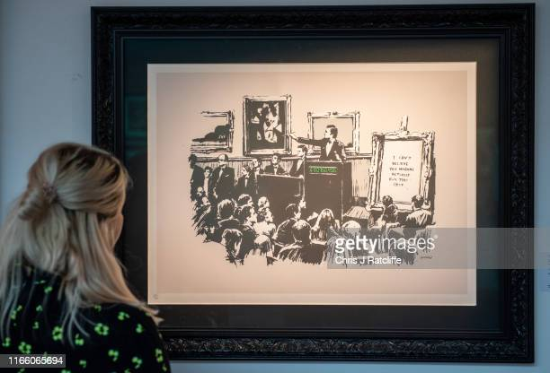 Woman looks at Morons by Banksy during a preview of the Banksy/Online sale at Sotheby's on September 5, 2019 in London, England. Exhibitions are now...