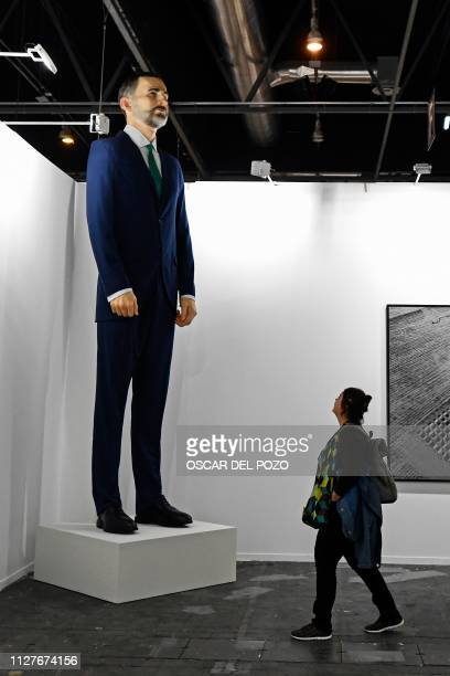 A woman looks at Ninot a giant sculpture depicting Spain's King Felipe VI by artists Santiago Sierra and Eugenio Merino during preparations for the...