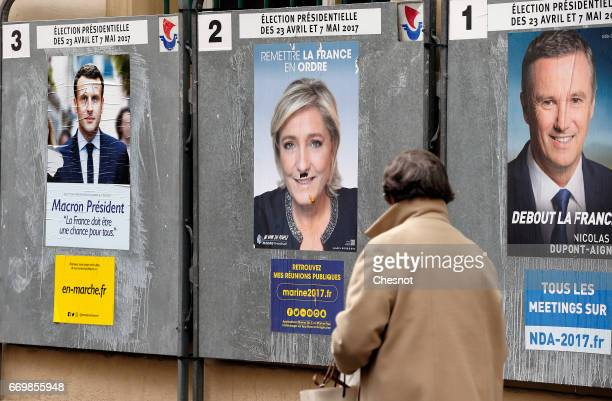 A woman looks at official campaign posters of Marine Le Pen French National Front and political party leader Emmanuel Macron head of the political...