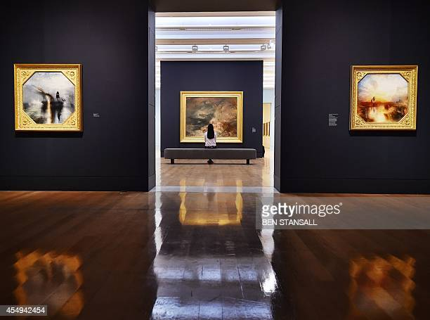 A woman looks at painting by British artist JMW Turner entitled 'Disaster at Sea' alongside 'Peace Burial at Sea and 'War The Exile and Rock Limpet'...