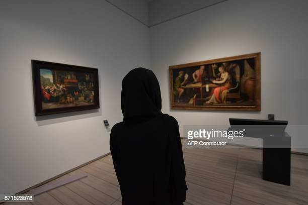 Woman looks at paintings at the Louvre Abu Dhabi Museum during a media tour on November 6, 2017 prior to the official opening of the museum on...