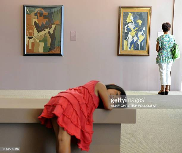 A woman looks at paintings by Spanish painter and sculptor Juan Gris on July 28 2011 at the Paul Valery museum in Sete southern France AFP PHOTO /...