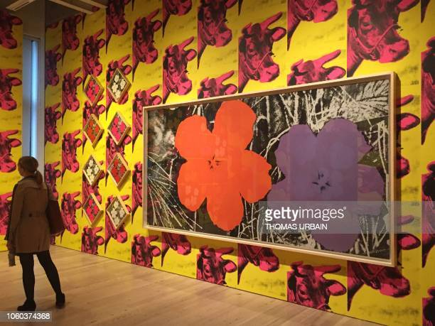 A woman looks at paintings from the 'Flower' series against a backdrop of 'Cow Wallpaper' by late US artist Andy Warhol during a press preview of the...