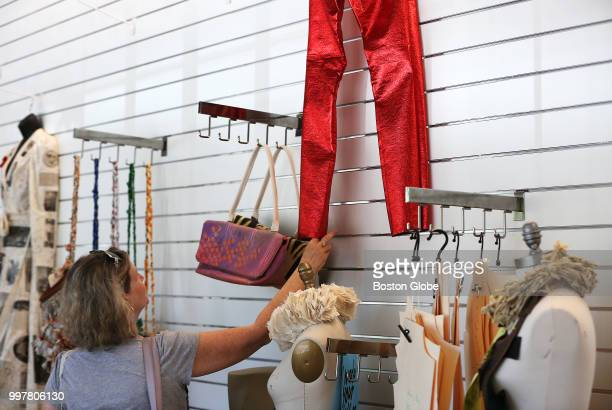 A woman looks at pants made out of a coated cotton remnant by Diana Jaye Coluntino at the opening of UMass Lowell's Fabric Discovery Center in Lowell...