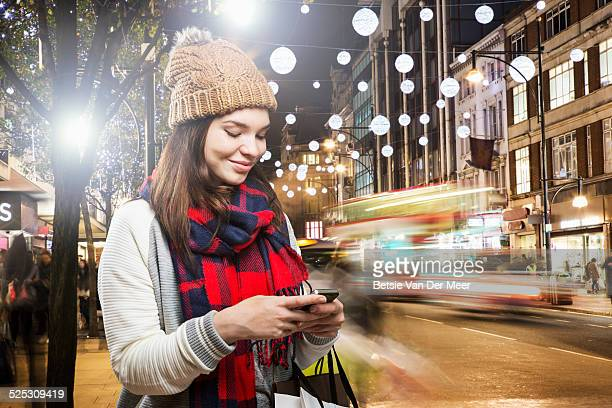 Woman looks at phone in busy street at night.