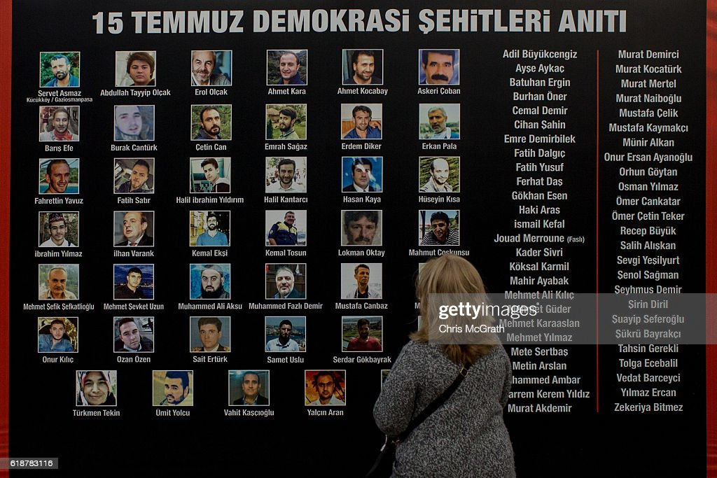 A woman looks at photographs of people killed on the night of the July 15 coup attempt on a board in a public square in the Gaziopasa neighbourhood on October 23, 2016 in Istanbul, Turkey. Public boards and posters showing the faces and names of the ' July 15 Martyrs' have appeared in public spaces across major Turkish cities. Since the failed coup attempt on July 15, 2016 which saw 240 people killed including 173 civilians, Turkish authorities initiated a state of emergency, leading to an unprecedented crackdown on individuals and organizations with links to US-based cleric Fethullah Gulen and his organization blamed for instigating the uprising. The purge, targeting teachers, journalists, soldiers, judges, academics, police, military leaders, schools and universities has so far seen approximately 100,000 people dismissed, 70,000 detained, 32,000 arrested, 130 media outlets closed and some 15 universities shuttered. The failed coup and subsequent purge only appears to have further bolstered the president's popularity and increased nationalism across the country with July 15th having been marked as a new national holiday. Turkish flags, already prominently displaying all over have increased in numbers, as well as posters of those killed fighting the coup plotters appearing in train stations and public squares. The Bosphorus Bridge in Istanbul, which saw heavy fighting during the coup has been renamed the '15th July Martyr's Bridge'. These changes, follow a year of instability in the country with constant terrorist attacks, an economic downturn, plummeting tourism, and a refugee crisis, all contributing to Turkish society undergoing its most dramatic restructuring in decades.