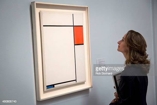 A woman looks at Piet Mondrian's 1927 piece Composition with Red Blue and Grey estimated to sell for between £13£18 million on display at Sotheby's...